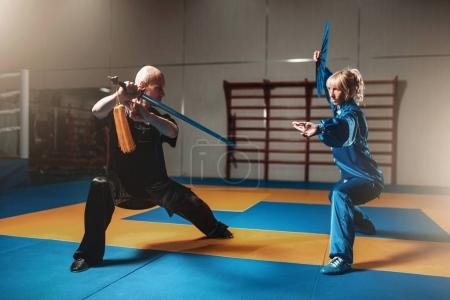 Photo for Male and female wushu fighters exercising with swords, martial arts culture - Royalty Free Image