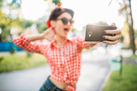 Photo for Attractive young woman with pin-up makeup and hairstyle taking selfie with smartphone, fifties american fashion in summer park - Royalty Free Image