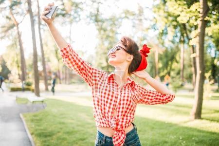 Photo pour Jeune femme attirante avec pin up maquillage et coiffure prenant selfie avec smartphone, fifties mode américaine dans le parc de l'été - image libre de droit