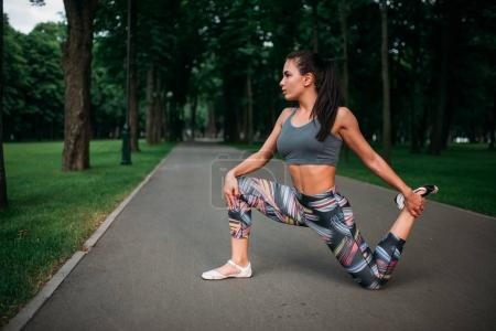Photo for Athletic young woman exercising outdoor, fitness training in summer park - Royalty Free Image