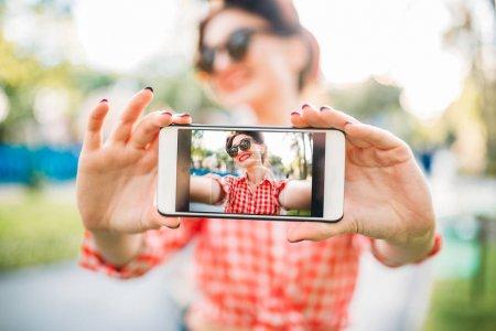 Photo pour Jeune femme attirante avec pin up maquillage et coiffure prenant selfie avec le smartphone, la cinquantaine de mode américaine - image libre de droit