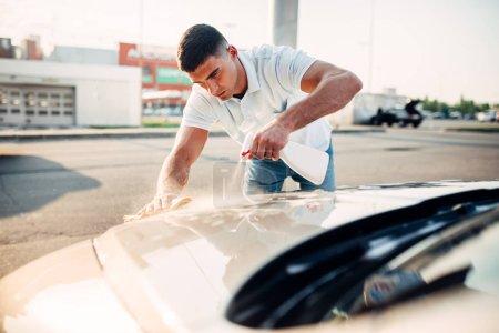 Photo for Man polishing car at carwash station. Rubbing vehicle with car polish - Royalty Free Image