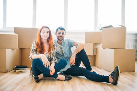 Photo for Happy couple sitting on floor with cardboard boxes in new apartment, moving to new house, housewarming concept - Royalty Free Image
