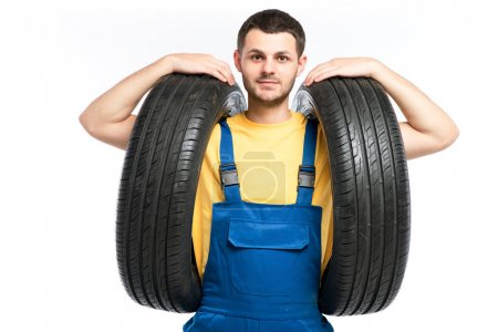Photo for Repairman in blue uniform with tires posing against white background, tire service and wheel mounting concept - Royalty Free Image