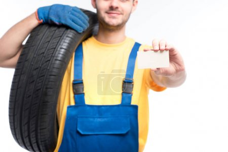 repairman in blue uniform with tire