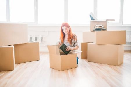 Photo for Beautiful happy young woman unpacking cardboard boxes in new apartment, moving to new house, housewarming concept - Royalty Free Image