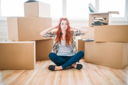 Photo for Beautiful tired young woman sitting near cardboard boxes in new apartment, moving to new house, housewarming concept - Royalty Free Image