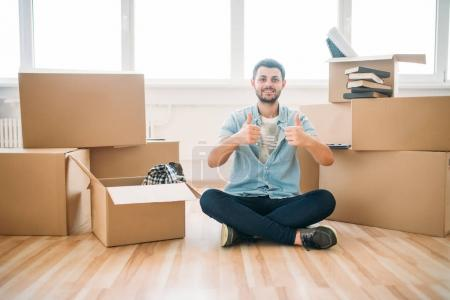 Photo for Happy young man sitting near cardboard boxes in new apartment, moving to new house, housewarming concept - Royalty Free Image