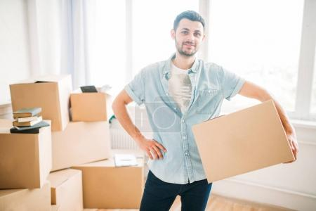 Photo for Young man holding cardboard box in new apartment, moving to new house, housewarming concept - Royalty Free Image