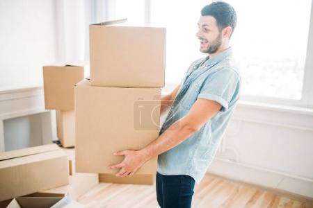 man sitting holding cardboard boxes