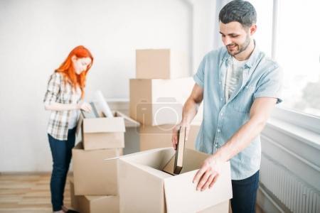 Photo pour Couple heureux déballage des boîtes en carton dans un appartement neuf, passage à la nouvelle maison, notion de pendaison de crémaillère - image libre de droit