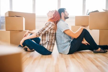 couple with cardboard boxes in new apartment