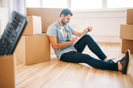 Photo for Young man sitting on floor near cardboard boxes in new apartment, moving to new house, housewarming concept - Royalty Free Image