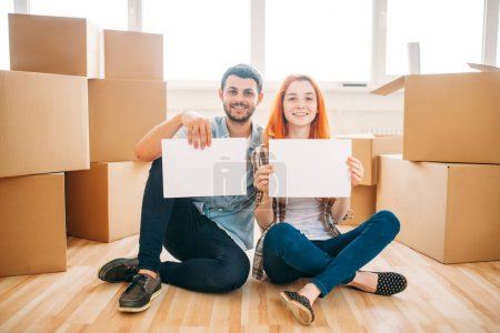 Photo for Happy couple sitting on floor with cardboard boxes in new apartment and holding blank paper sheets in hands, moving to new house, housewarming concept - Royalty Free Image