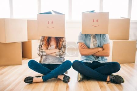 couple with cardboard boxes on heads