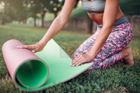 Foto de Mujer hermosa joven balanceo estera de la yoga en el parque de verano, al aire libre del entrenamiento de la mañana - Imagen libre de derechos