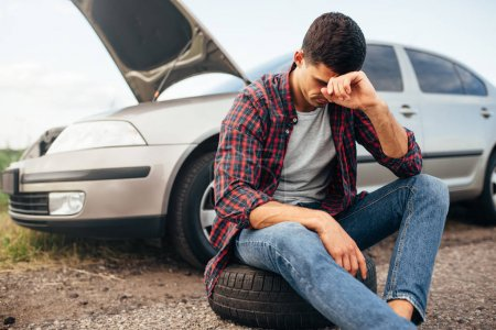 Photo for Tired depressed man sitting on tire, broken car with open hood on background - Royalty Free Image