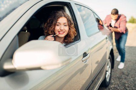 Photo for Man pushing broken car down the road, woman driving and painting lips. Vehicle in trouble - Royalty Free Image