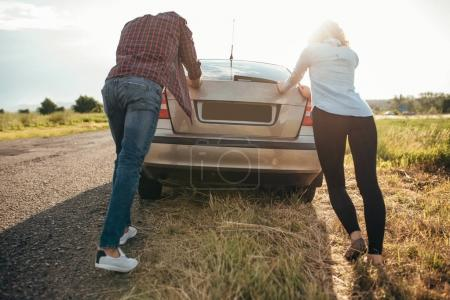Photo for Young man and woman pushing broken car down the road, back view. Vehicle with trouble - Royalty Free Image