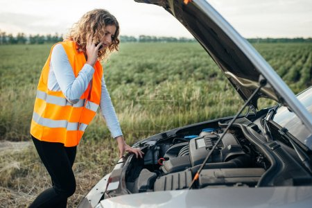 Photo for Young woman in orange high-visibility vest calling to car emergency service, vehicle with open hood on roadside. Trouble with car on road - Royalty Free Image
