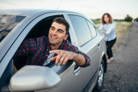 Photo for Woman pushing broken car down the road, man driving. Vehicle in trouble - Royalty Free Image