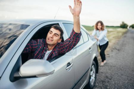 man driving and woman pushing car