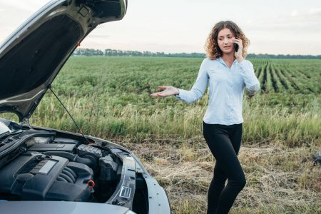 Photo for Young woman calling to car emergency service, vehicle with open hood on roadside. Trouble with car on road - Royalty Free Image