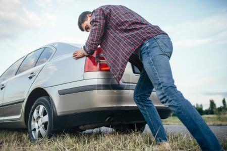 Photo pour Jeune homme poussant voiture cassée sur la route. Véhicule avec problème - image libre de droit