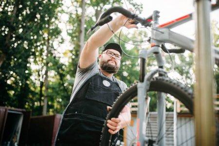 Photo pour Mécanicien professionnel de mâle en tablier réglage de vélo. Barbu de service travaillant avec roue et guidon - image libre de droit