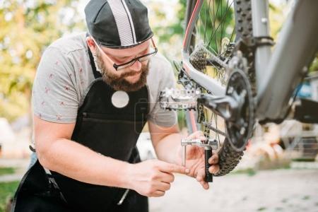 male mechanic repairing bicycle