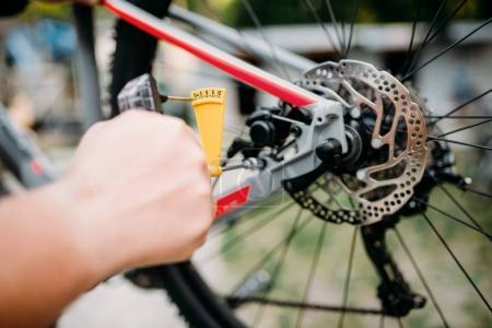 Photo pour Mécanicien masculin professionnel réparation vélo. Main de l'homme de service travaillant avec freins à disque arrière - image libre de droit
