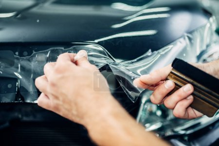 worker installing car protection film