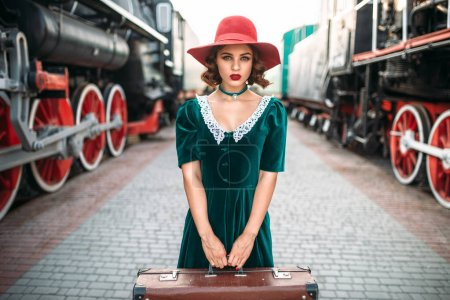 Photo for Beautiful young woman in red hat and green dress carrying suitcase against old steam locomotives. Retro train. Railroad journey - Royalty Free Image