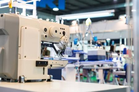 modern sewing machine closeup, dressmaker equipment, cloth industry. Factory production, sew manufacturing