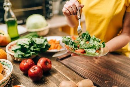 Photo pour Femme cuisine salade dans la cuisine, des aliments sains. Régime végétarien, légumes et fruits frais sur table en bois - image libre de droit