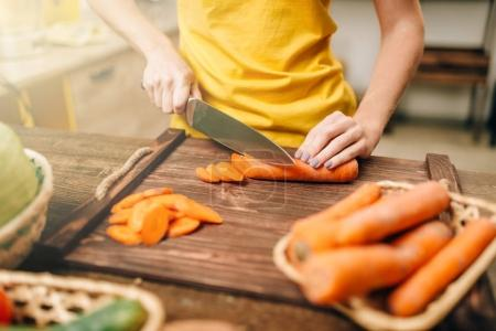 hands of woman cutting carrot on wooden table, cooking organic food. Vegetarian diet, healthy lifestyle
