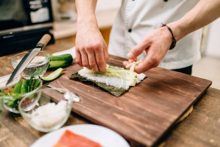Photo for Male cook making sushi with avocado on wooden table. Traditional japanese cuisine, seafood - Royalty Free Image