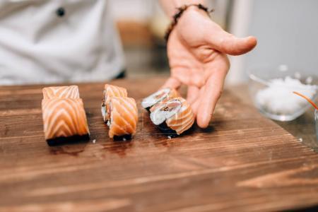Photo pour Cuisinier homme faire des sushis sur table en bois. Cuisine japonaise traditionnelle, fruits de mer - image libre de droit