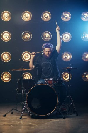 bearded drummer with colorful hair, rock performer on the stage with lights. Music concert in night club