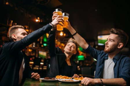 Photo for Happy company of friends raised their glasses with beer in sport bar, leisure of football fans - Royalty Free Image