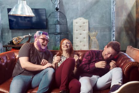 Photo for Happy friendship, cheerful friends having fun on sofa, home party - Royalty Free Image