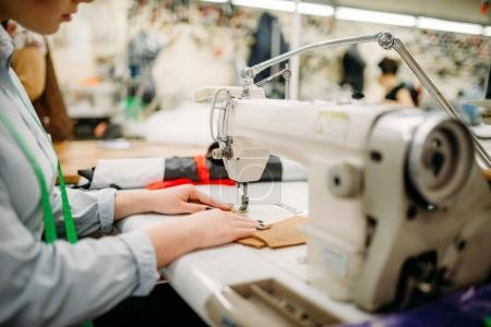 Photo for Needlewoman sewing textile on sewing machine. Tailoring or dressmaking on clothing factory - Royalty Free Image