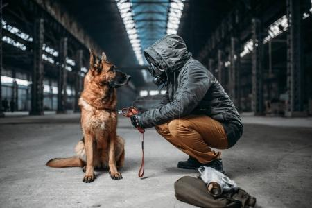 stalker in gas mask and dog, friends in post apocalyptic world. Post-apocalypse lifestyle on ruins, doomsday concept