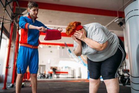 Photo pour Instructeur forçage grosse femme d'exercer, dur d'entraînement en gymnase - image libre de droit