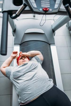 fat tired woman lying on treadmill after running in gym