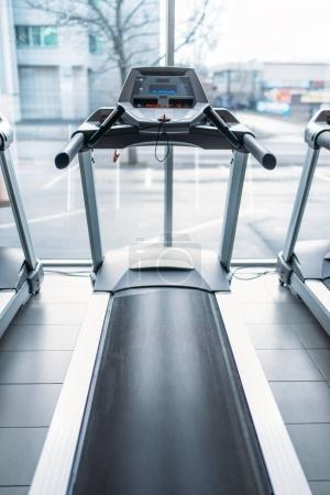 Treadmill machine against big window, gym interior, jogging track, stationary running simulator, sport equipment