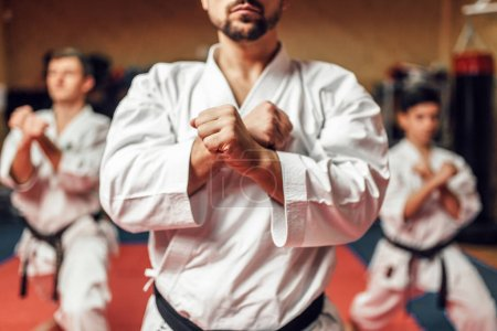 Martial arts karate master and disciples in white uniform and black belts, fight training in gym