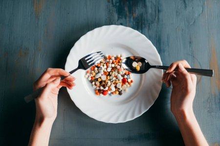 female hands with spoon and fork, plate full of drugs, weight loss diet concept