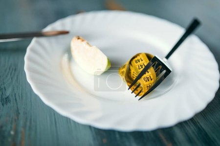 measuring tape on fork and slice of apple , weight loss concept