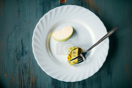 Photo for Measuring tape on fork and slice of apple , weight loss concept - Royalty Free Image